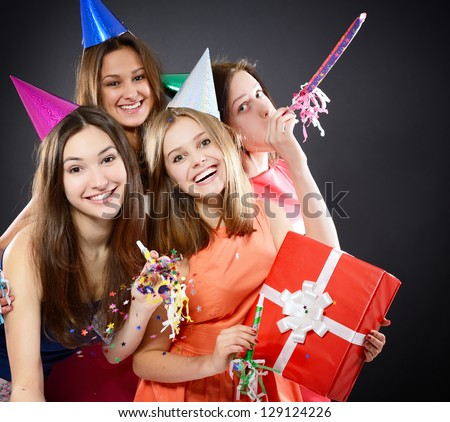 Joyful happy smiling teen girls have fun on birthday party, over black - stock photo