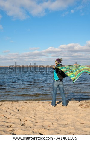 Joyful happy woman having fun, playing with a veil in the wind, while relaxing at the coast. Beautiful autumn day.