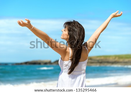 Joyful happy woman raising arms to the sky on summer. Beautiful and blissful caucasian girl on beach vacation. Playa de Verdicio, Asturias, Spain. - stock photo