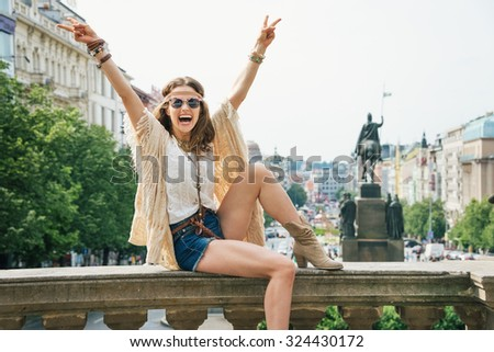 Joyful hippie young woman tourist showing victory gesture on Wenceslas Square in Prague. In the background Saint Wenceslas statue in Prague. Tourism travel concept. - stock photo