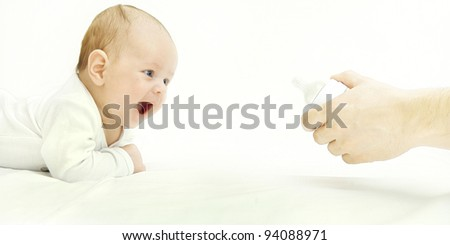 Joyful infant crawling on the floor to the bottle with a pacifier in  a parent hand on a white background. The concept of a happy childhood - stock photo