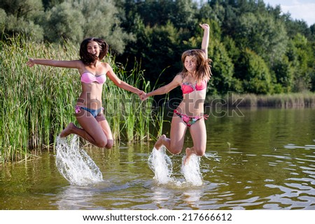 joyful jump: 2 pretty sexy girlfriends in bikini having fun happy smiling jumping in the water and looking at camera on summer outdoors copy space background, portrait - stock photo