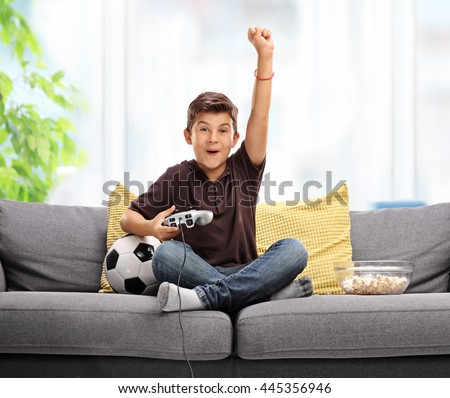Joyful kid playing football video game and celebrating a goal with his fist in the air seated on a gray sofa - stock photo