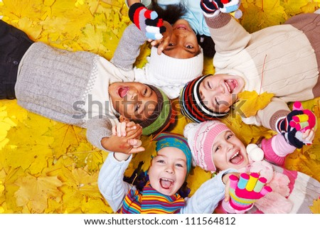 Joyful kids lie on yellow leaves - stock photo