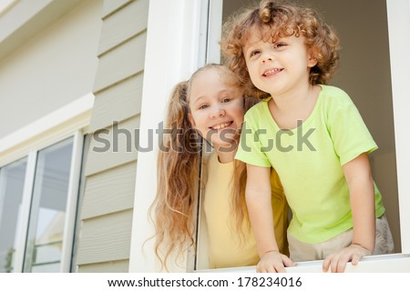 Joyful kids looking out the window at home. Brother And Sister Together Forever - stock photo