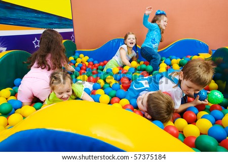 Joyful kids playing in the pool with colorful balls - stock photo