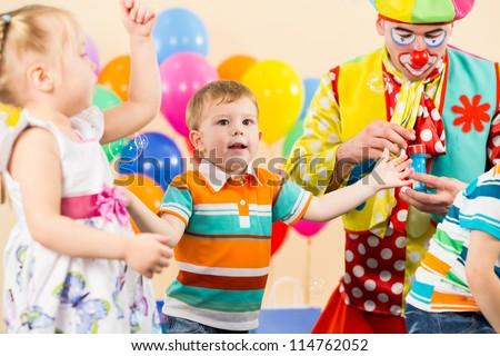 joyful kids with clown on birthday party - stock photo