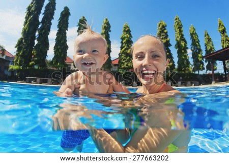 Joyful little baby having a fun and laughing with happy smiling mother in swimming pool with blue water during summer family vacation with child in a tropical resort,  underwater portrait - stock photo