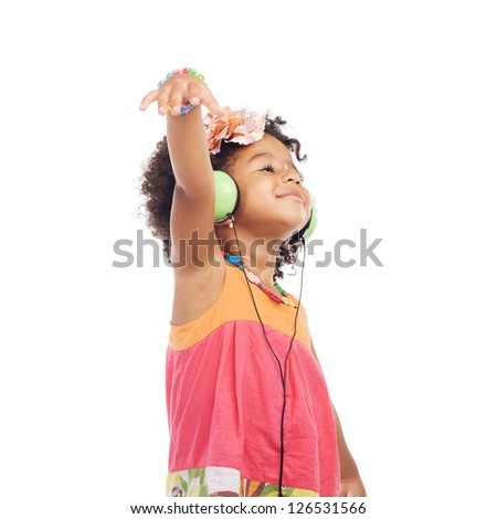 Joyful little girl in headphones is dancing against white background - stock photo
