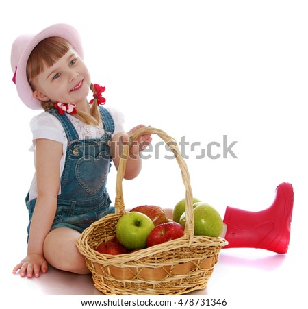 Joyful little girl with a basket which contains apples . Girl sitting on the floor . on the head of the girls pink hat-Isolated on white background