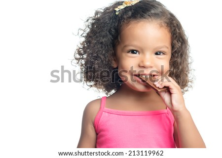 Joyful little girl with an afro hairstyle eating a chocolate bar isolated on white - stock photo
