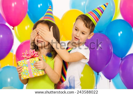 Joyful little kid girl receiving gifts at birthday party. Holidays concept.