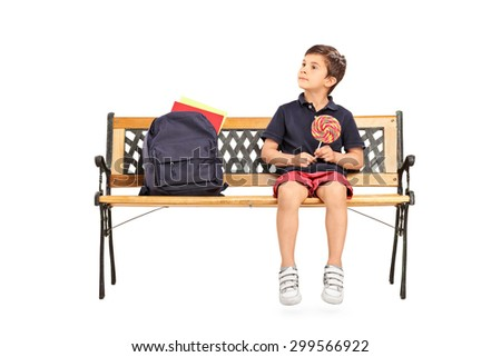 Joyful little schoolboy sitting on a wooden bench and holding huge lollipop isolated on white background - stock photo