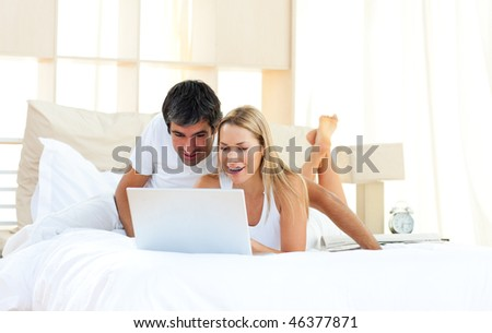 Joyful lovers using laptop lying on bed at home - stock photo
