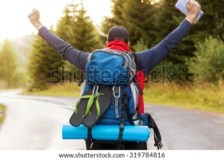 Joyful male back packer is arriving to the end point of his journey. - stock photo