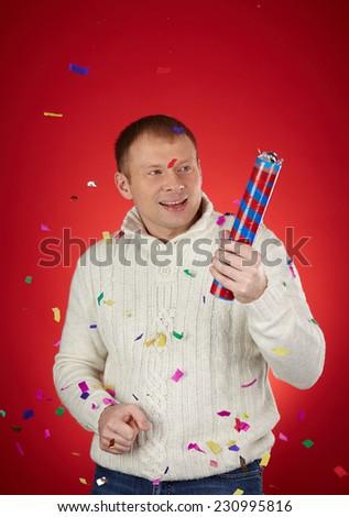 Joyful man in white knitted sweater holding confetti cracker - stock photo