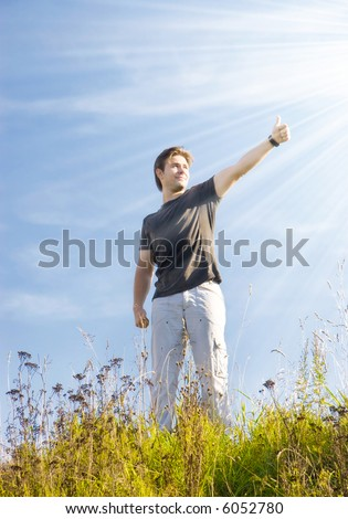 Joyful man showing excellent sign. Bright sun with rays. - stock photo