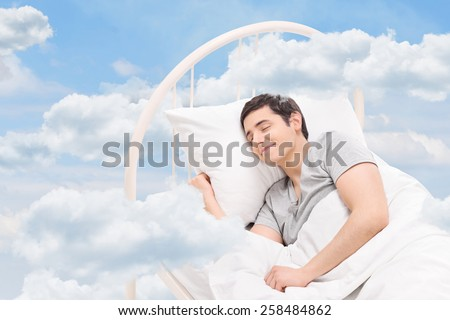 Joyful man sleeping on a bed in the clouds  - stock photo