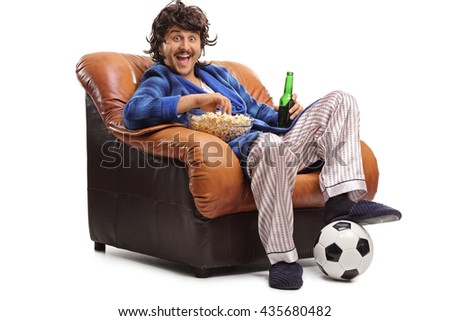 Joyful man watching football on TV seated in an armchair and eating popcorn isolated on white background - stock photo