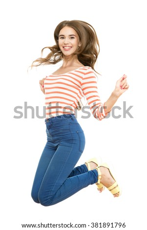 Joyful moments. Full length portrait of a young beautiful brunette girl wearing a white red frock and jeans jumping and smiling happily holding hand above her head, isolated on white background - stock photo