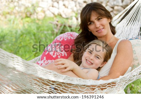 Joyful mother and young daughter relaxing together on a hammock in a holiday home garden with green grass during a sunny summer day. Family activities and lifestyle outdoors. - stock photo