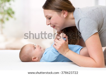 joyful mother playing and doing gymnastics her baby infant