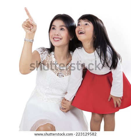Joyful mother with her daughter pointing and looking at copyspace in studio - stock photo