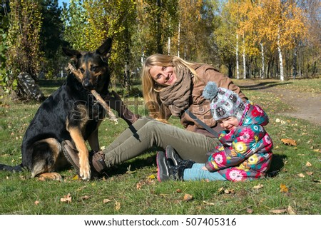 Joyful mother with little daughter having fun with a dog in the autumn park.