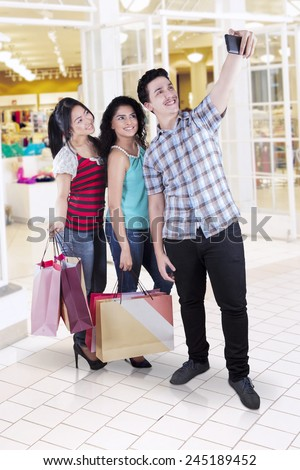 Joyful multi cultural people taking pictures while carrying shopping bags in the mall - stock photo