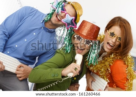 Joyful new year's eve office band, workers using phone and keyboard as instrument, singing, having fun in party accessories. - stock photo