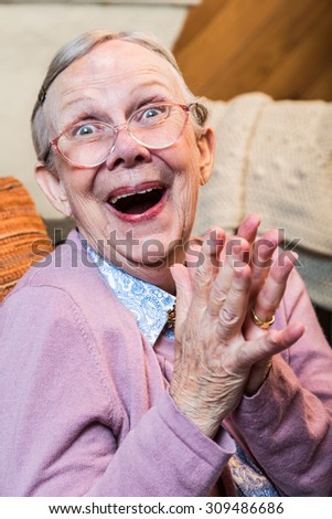 Joyful old woman in pink sweater with hands together - stock photo