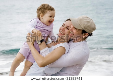 Joyful parents playing with adorable baby outdoors and laughing - stock photo