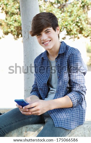 Joyful portrait of a young teenager student boy sitting by a tree in a college campus using a smartphone mobile to network and browse the internet during a sunny day. Technology outdoors. - stock photo