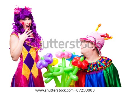 Joyful posing clowns in love with colorful flowers on isolated white - stock photo