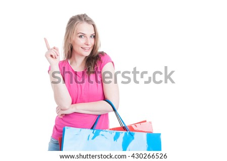 Joyful pretty female carrying shopping bags and having an idea and pointing finger up with copyspace isolated on white background - stock photo