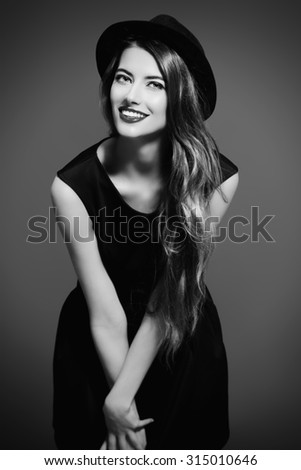 Joyful pretty girl wearing black dress and black classic hat smiling at camera. Beauty, fashion concept. Hipster style. - stock photo