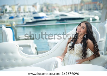 Joyful pretty woman wearing beautiful elegant dress, enjoying relaxed sunny day out at marina, with boats as background. Beautiful sunset at the yacht club - stock photo