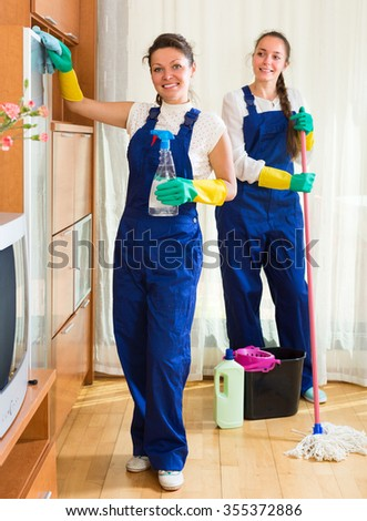 Joyful professional cleaners washing apartment with rags and mop. Selective focus