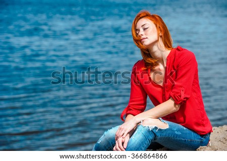 Joyful redhead woman sitting comfortably, feeling serene and free and enjoying a sunny day at the beach. - stock photo