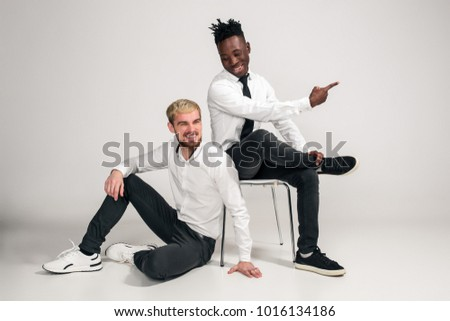 Joyful relaxed african and caucasian boys in white and black office clothes laughing and posing at white studio background with copy space