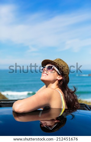 Joyful relaxed woman on summer travel vacation to the coast  leaning out car sunroof towards the sea. - stock photo