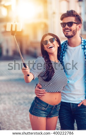 Joyful selfie. Joyful young loving couple making selfie on smart phone while standing outdoors - stock photo