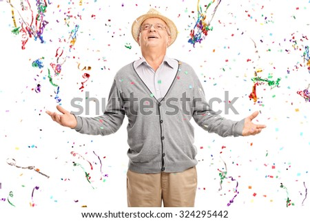 Joyful senior gentleman standing in a bunch of confetti streamers isolated on white background - stock photo