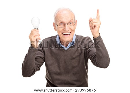 Joyful senior holding a light bulb and gesturing with his hand as if he is having an idea isolated on white background - stock photo