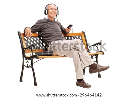 Joyful senior sitting on a wooden bench and listening to music on his cell phone isolated on white background