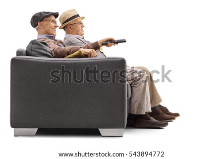 Joyful seniors seated on a sofa watching television with one of them holding a remote isolated on white background