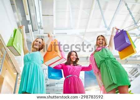 Joyful shopaholics holding paperbags in raised hands - stock photo