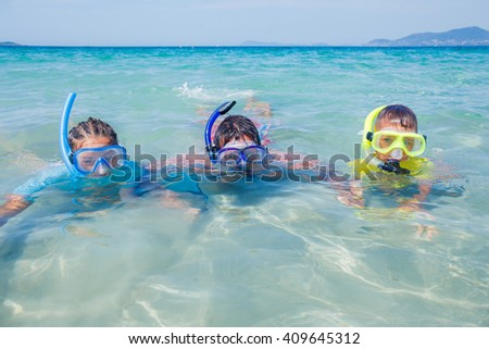 Joyful sister and brother with father scuba diving in the clear sea.