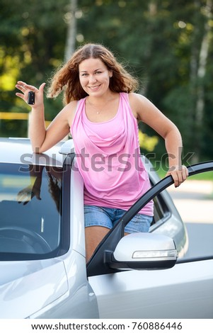 Joyful smiling girl with car keys in hand standing on footboard of vehicle