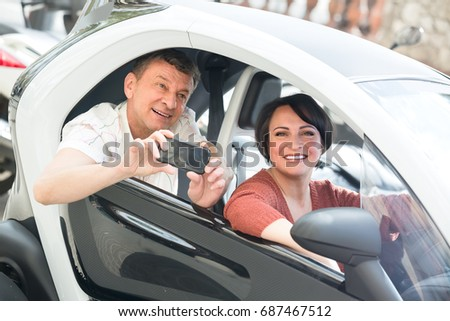 Joyful smiling mature spouses in twizy electric outside